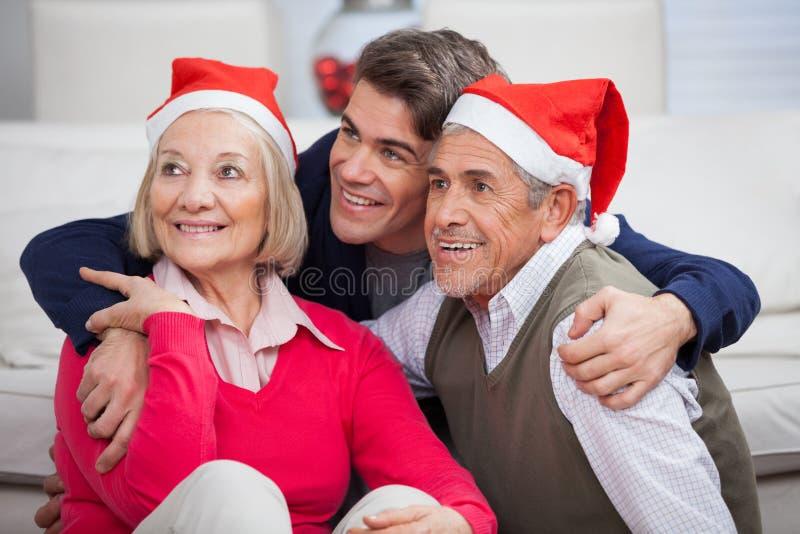 Kochający syn Z rodzicami Jest ubranym Santa kapelusze obraz royalty free