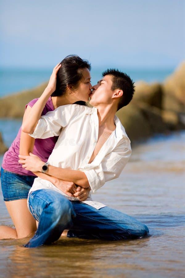 kochających kucań para młoda całuje obraz stock