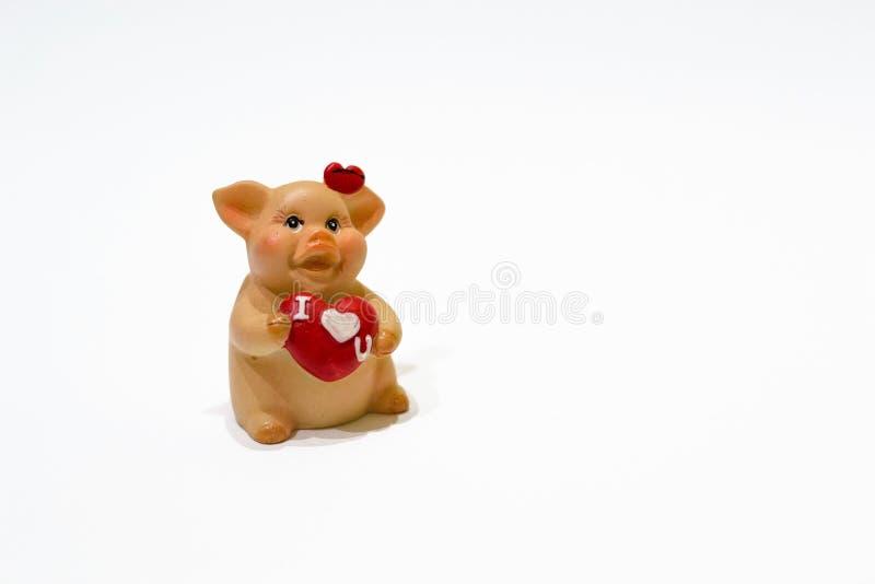kocham cię Zbliżenie ceramiczna zabawkarska świnia z czerwonym sercem odizolowywającym na białym tle Szczęśliwy walentynka dzień, obrazy royalty free