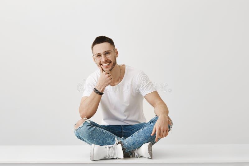 Kocham słucham twój opowieści Salowy strzał przystojny młody człowiek siedzi na podłoga z krzyżować nogami z szczecina zdjęcie royalty free