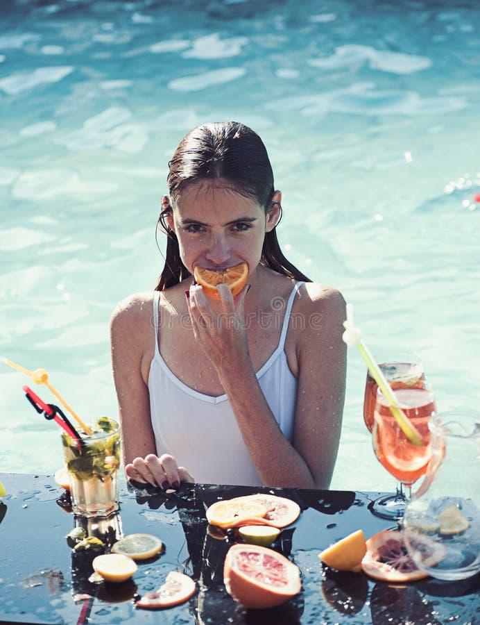 Kocham wydawać czasu poolside młoda kobieta pije koktajle w swimsuit podczas gdy relaksujący w basenie obraz stock