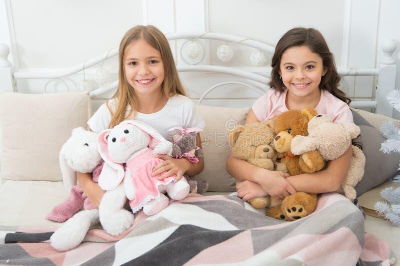 Kochamy boże narodzenia Mała dziewczyny sztuka z zabawkami Szczęśliwi dzieciaki w łóżku przy choinką Małe dzieci cieszą się boże  fotografia stock