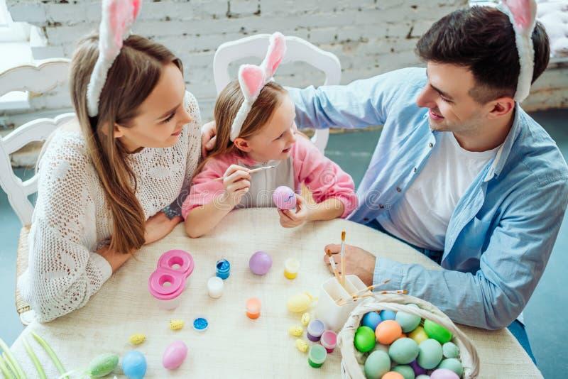 Kochamy piękne tradycje Mama i córka malujemy jajka, tatów chwyty domu dekoracyjny królik obrazy stock