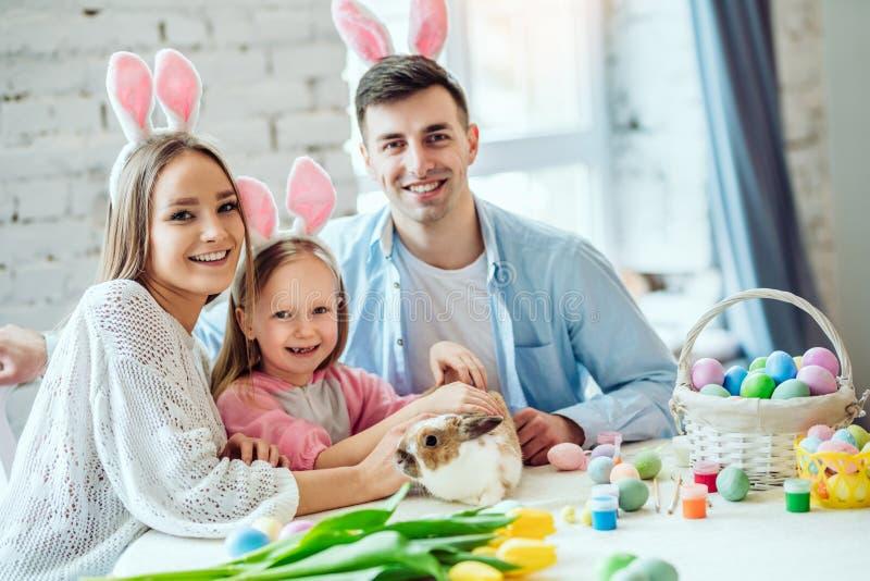 Kochamy piękne tradycje Mama i córka malujemy jajka, tatów chwyty domu dekoracyjny królik zdjęcie stock