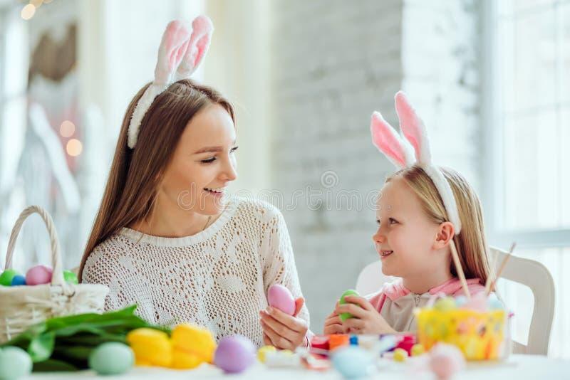 Kochamy piękne tradycje Mama i córka malujemy jajka, tatów chwyty domu dekoracyjny królik zdjęcia royalty free