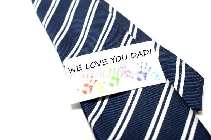 Kochamy was tata z kolorową ręka druków etykietką na błękitnym krawacie nad w zdjęcia royalty free