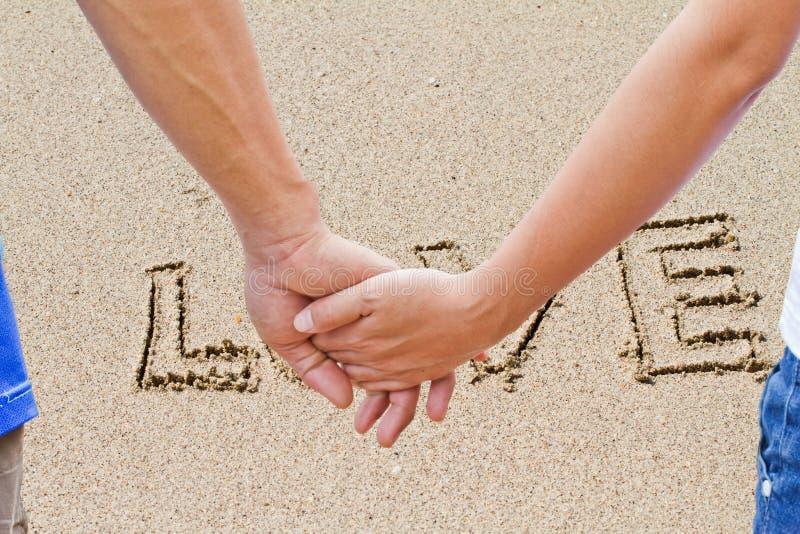 Kochanek Pisać w piasku na plaży fotografia royalty free