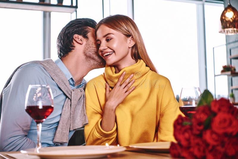 Kochankowie przy początkiem historia miłosna - Przystojny mężczyzna szepcze w ładnym kobieta ucho obraz stock