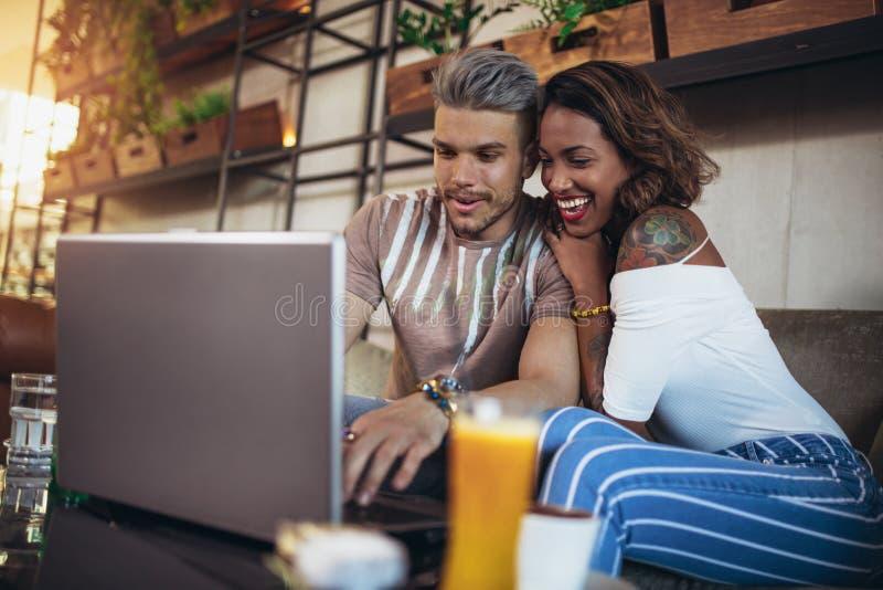 Kochankowie wydaje czas w cukiernianych dopatrywanie środkach na laptopie fotografia stock