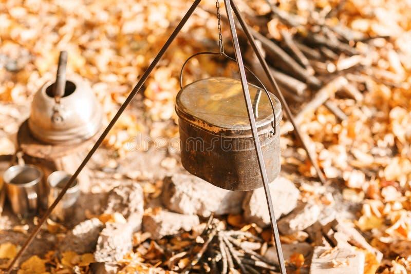 Kochen über einem Lagerfeuer in einem Roheisentopf Roheisentopf für die Suppe, die über dem Feuerlagerfeuer hängt lizenzfreie stockfotografie