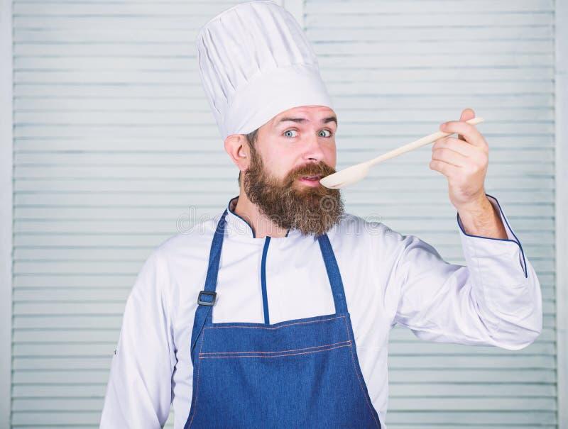 Kochen als Berufsbesetzung Des b?rtigen h?lzerner L?ffel Chefgriffs des Hippies K?chengeschirr und kochen Konzept L?sst Versuch stockfotografie