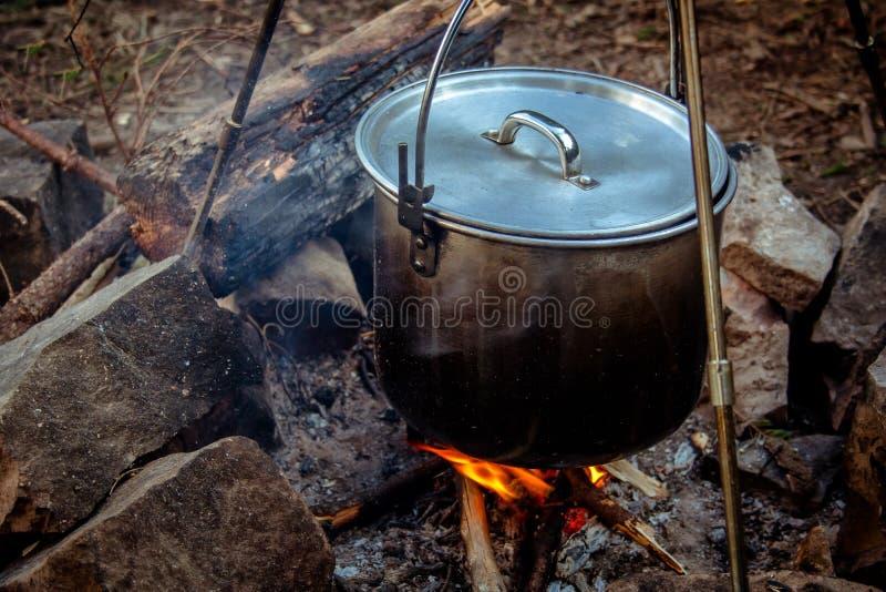 Kochen der Mahlzeit in einem Kessel auf brennendem Lagerfeuer im wilden Kampieren lizenzfreies stockbild