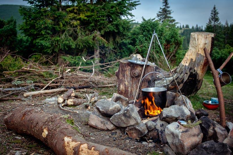 Kochen der Mahlzeit in einem Kessel auf brennendem Lagerfeuer im wilden Kampieren lizenzfreie stockfotografie