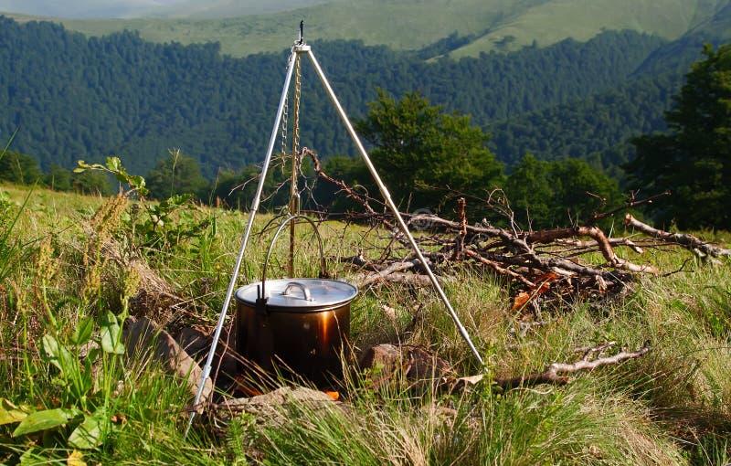 Kochen der Mahlzeit in einem Kessel auf brennendem Lagerfeuer im wilden Kampieren stockbild