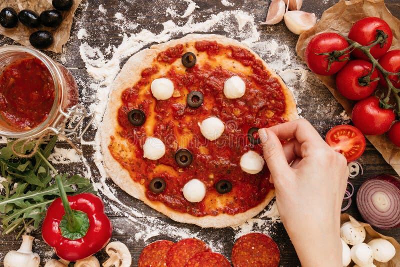 Kochen der Pizza Hände, die Bestandteile Pizza hinzufügen Pizza ingerdients auf dem Holztisch, Draufsicht stockbilder