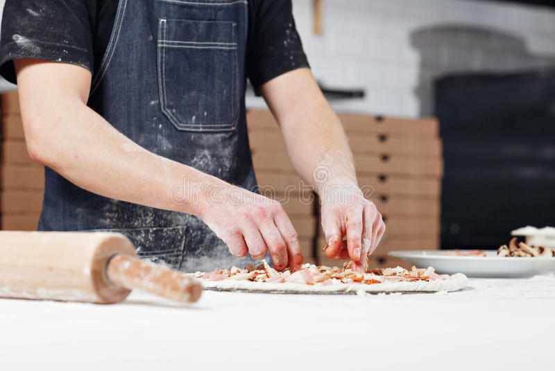Kochen der Pizza vereinbart Fleischbestandteile auf dem Teigvorformling Nahaufnahmehand des Chefbäckers im einheitlichen blauen S lizenzfreie stockbilder
