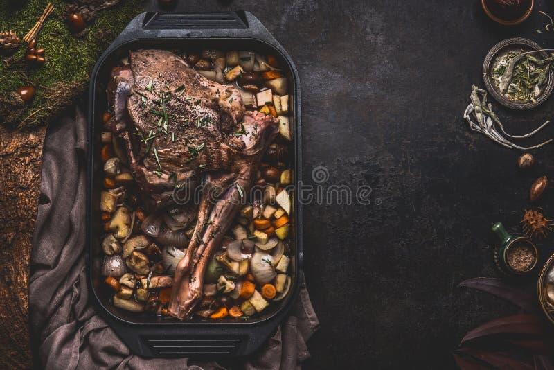 Kochen der Vorbereitung Wildbretbraten Beines von Rotwild mit dem Knochen in geworfenem Eisenstein mit Darmgemüse auf dunklem Küc lizenzfreies stockfoto