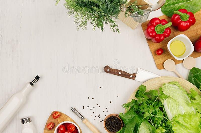 Kochen des frischen rohen Frühlingssalats des grünen und roten Gemüses, Gewürze, Öl mit hölzernem Küchengeschirr auf weißem hölze lizenzfreie stockfotos