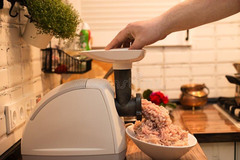 Kochen des Hackfleischs in einem elektrischen Fleischwolf auf dem K?chentisch lizenzfreie stockfotos