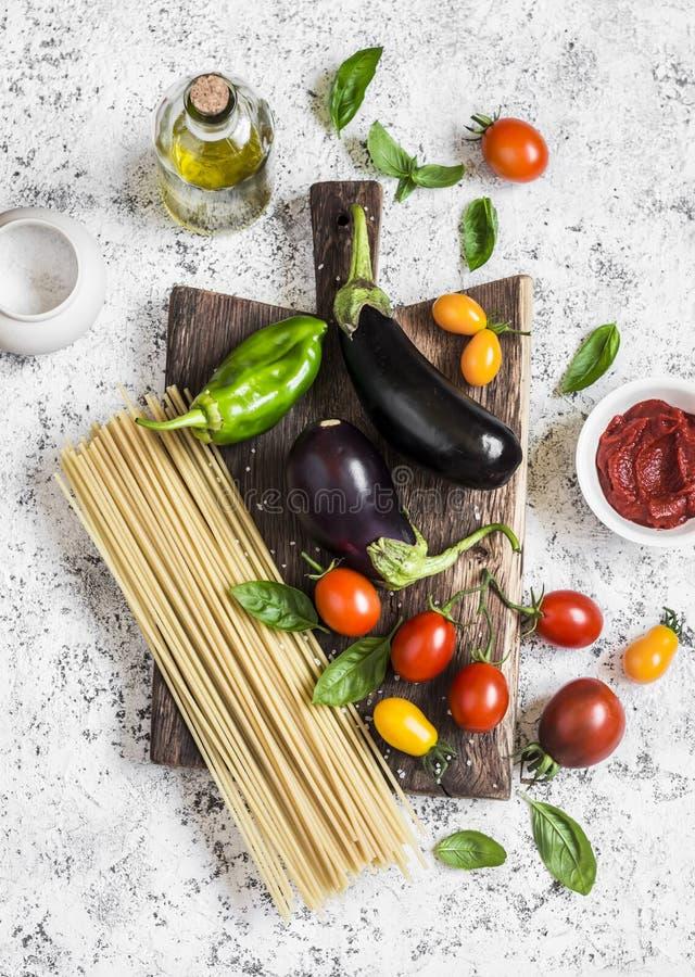 Kochen des Hintergrundes Rohe Bestandteile für Teigwaren an machen - Spaghettis, Aubergine, Tomaten, Pfeffer, Olivenöl, Tomatensa lizenzfreies stockfoto