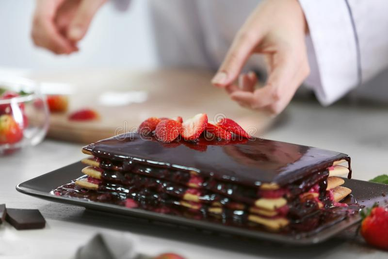 Kochen des Konzeptes Berufskonditor, der köstlichen Kuchen mit Erdbeere verziert, stockfoto