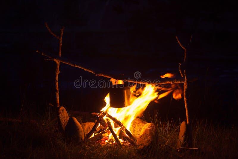 Kochen des Lagerlebensmittels im Großen Kessel auf offenem Feuer nachts stockfotos