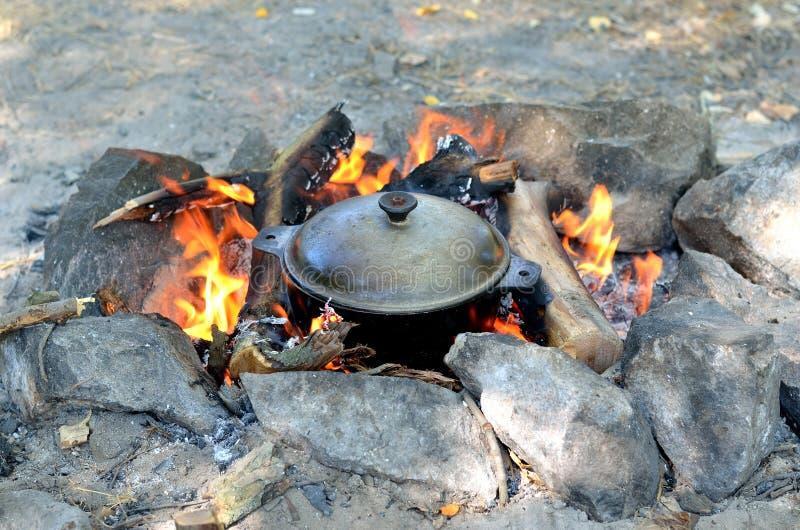 Kochen des Lebensmittels in einem Roheisentopf über einem offenen Feuer, wandernd stockbild
