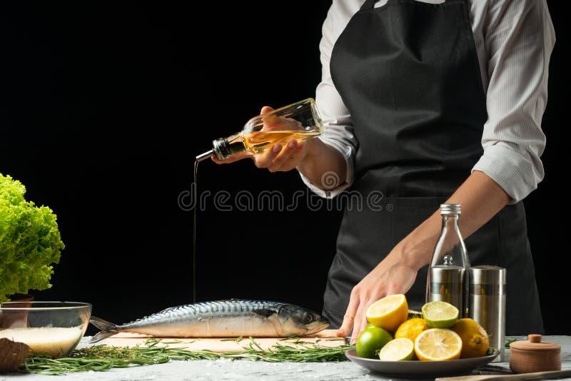 Kochen des Leiters der frischen Fische, die Chefsalzfische auf einem schwarzen Hintergrund mit Zitronen, Kalke lizenzfreies stockbild