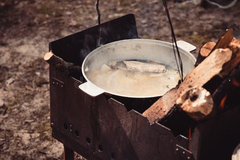 Kochen des Ohrs in einem Topf über Lagerfeuer lizenzfreies stockfoto