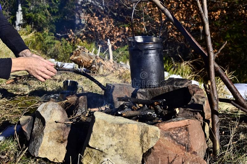 Kochen in einem Topf über Lagerfeuer in den Bergen lizenzfreie stockfotos