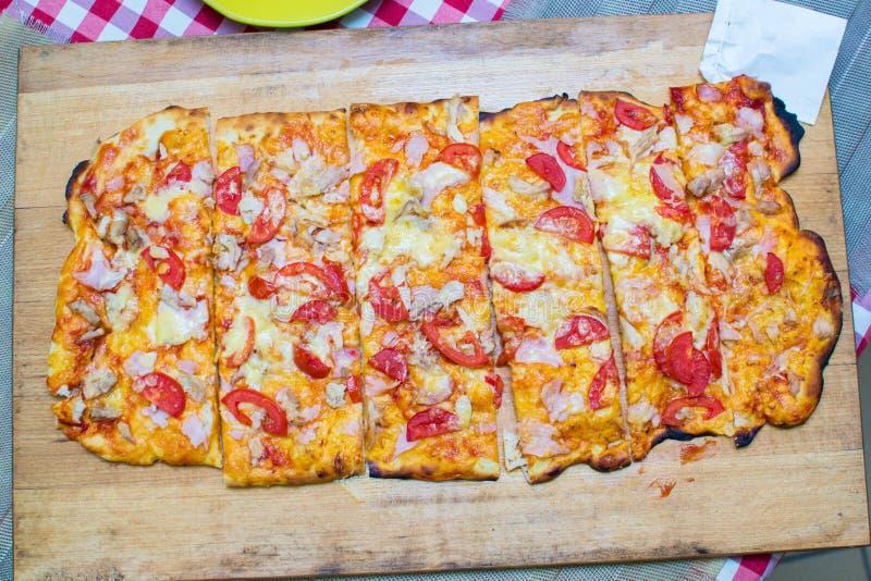 Kochen einer großen rechteckigen Pizza stockbilder