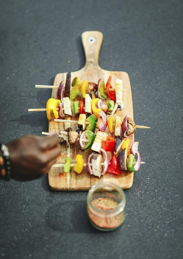 Kochen Sie das Hinzufügen des Gewürzes Grillaufsteckspindeln des strengen Vegetariers stockfotografie