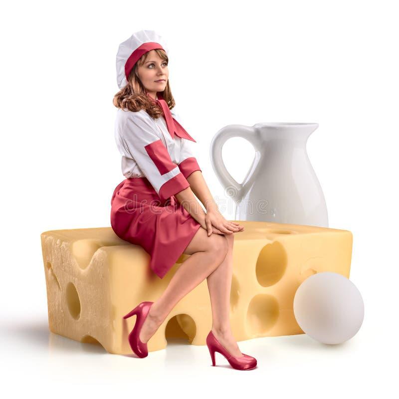 Kochen Sie das Mädchen, das auf einem Stück Käse auf lokalisiertem Hintergrund sitzt stockfoto