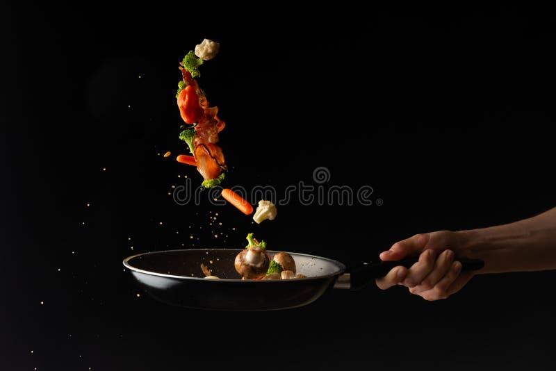 Kochen Sie das Vorbereiten von Speckscheiben mit Knoblauch und Peperoni und Brokkoli in einer Wanne lizenzfreies stockbild