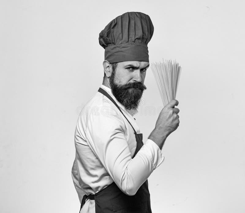 Kochen Sie mit strengem Gesicht in Burgunder-Uniform hält trockene Teigwaren lizenzfreie stockbilder