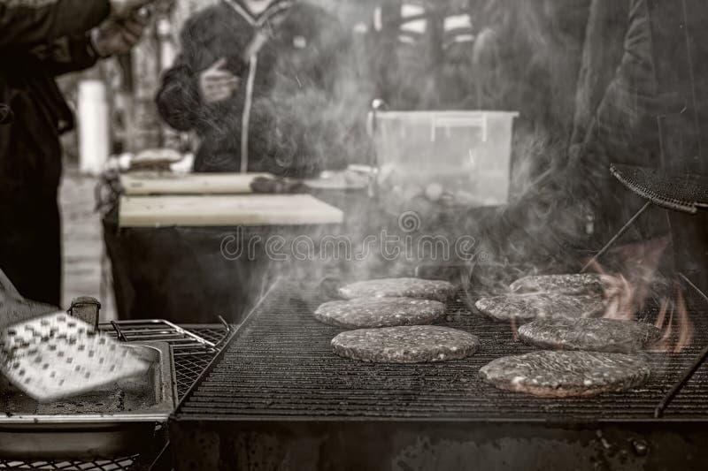 Kochen von Burgern auf einer Nachtstadtstraße lizenzfreie stockbilder