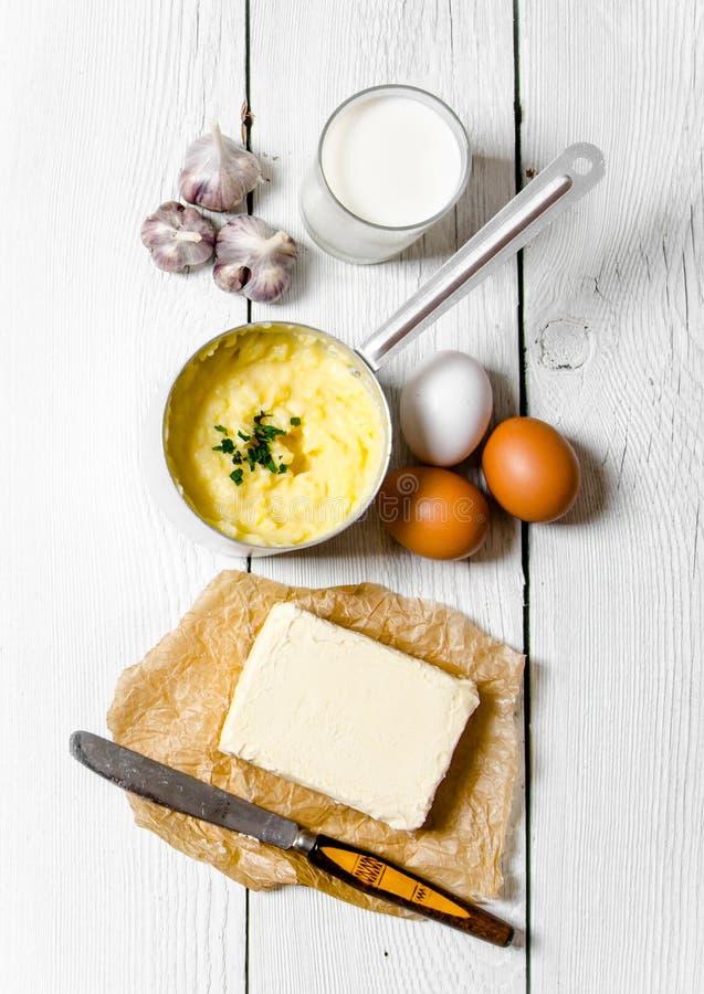 Kochen von Kartoffelpüreebestandteilen: Kartoffeln, Milch, Eier, Butter und andere auf einem weißen Holztisch lizenzfreie stockbilder