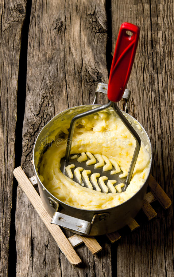 Kochen von Kartoffelpürees mit Stampfe auf hölzernem Hintergrund stockfotografie