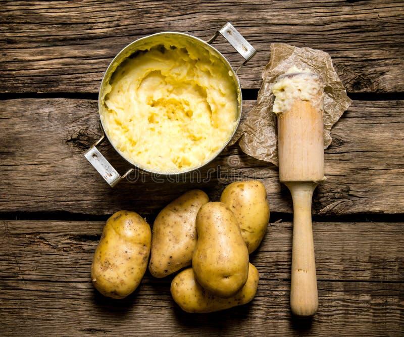 Kochen von Kartoffelpürees mit Stampfe auf hölzernem Hintergrund lizenzfreie stockfotos