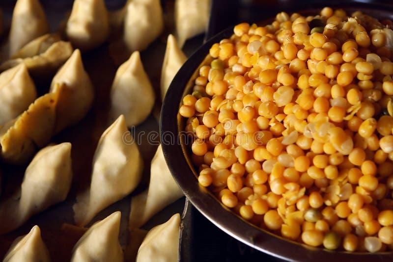 Kochen von Samosas mit Erbsen in der indischen Küche lizenzfreie stockfotografie