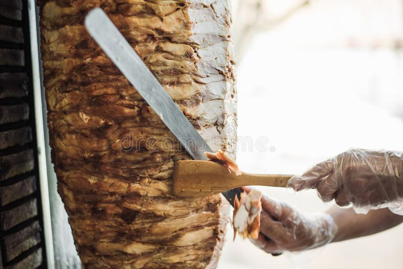 Kochen von shawarma und von ciabatta in einem Café Ein Mann im Wegwerfhandschuh-Schnittfleisch auf einer Aufsteckspindel stockfotos