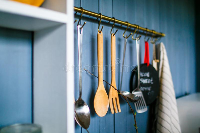 Kochende Geräte auf Metallhaken in der Küche lizenzfreies stockbild