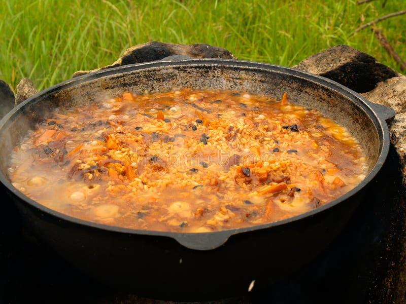 Kochendes pilau auf dem Feuer stockfotos