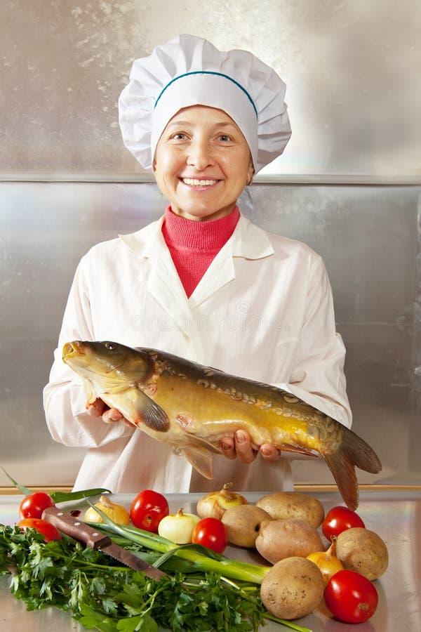Kochfrau mit Karpfen stockfotografie