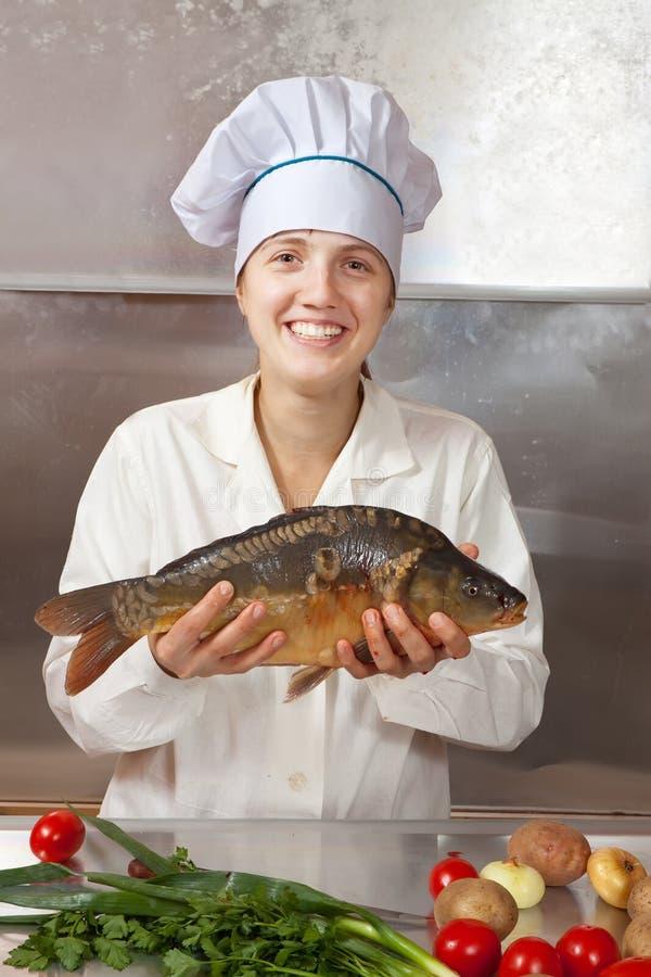 Kochfrau mit Karpfenfischen stockbilder