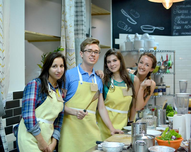 Kochkurs junge glückliche Freunde in der Küche stockbilder