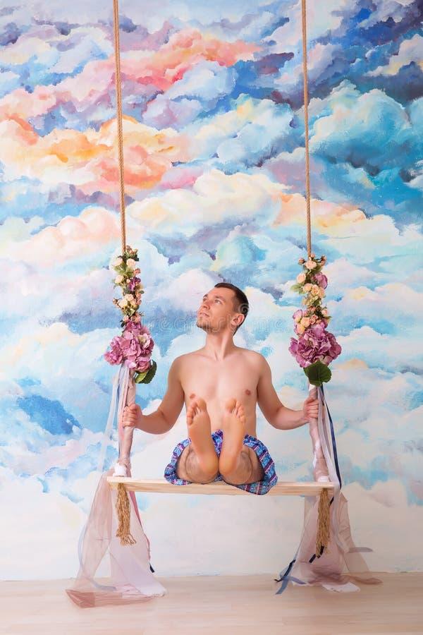 Kochliwy mężczyzna huśta się na drewnianej ławce w majtkach obrazy stock