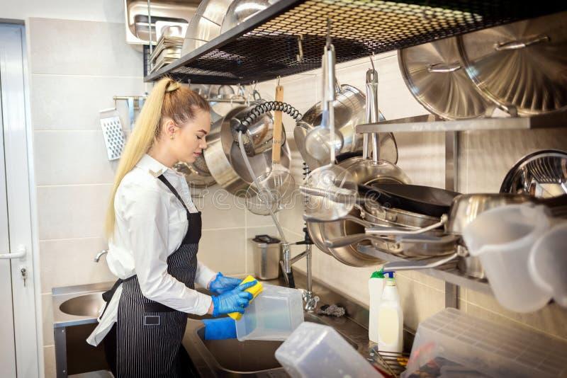 """Kock av tvättande disk för liten restaurang i vask på slutet arbetare för kök av för arbetsdags†som """"använder svampen till ren  royaltyfria bilder"""