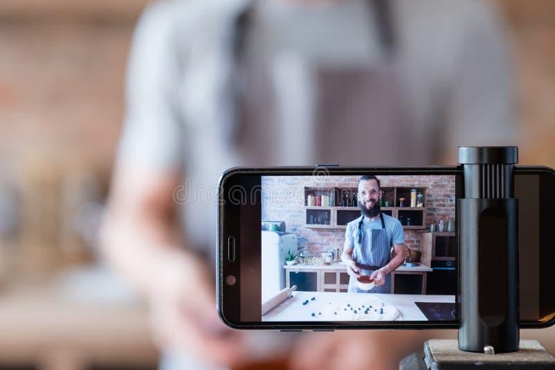 Kock för man för kamera för telefon för matbloggerström levande arkivbilder