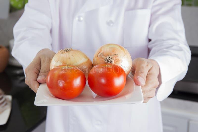 Kock framlagd lök och tomat arkivbilder